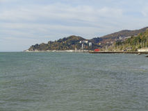 The coast Sochi, view from the sea. Wooded cape, houses, hotels, roads, beaches and piers Stock Photography