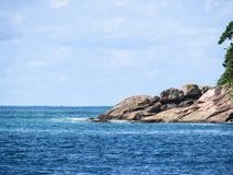 Shore of rocks in the sea with blue sky. Coast of stones in the sea, with blue sky, in sunny day Royalty Free Stock Photography