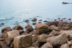 Coast stones. And sea wave over cloudy sky in summer stock images