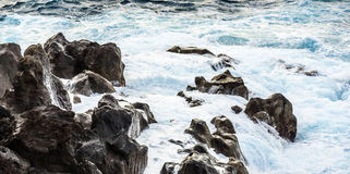 Coast with Stones of volcanic flow and ocean Royalty Free Stock Image