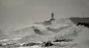 Coast with strong waves and lighthouse Royalty Free Stock Image