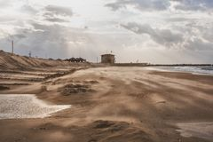 On the coast a strong wind blows with sand against the backdrop. Of the setting sun Stock Image
