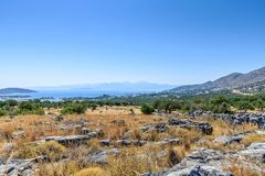 Coast from the top of a hill in Crete. View from scrubland  down to the Mediterranean Sea.  Rocks, overgrown with grass, are in the foreground with hills in the Stock Photo