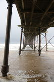 Coast tourism Yorkshire. A stormy looking day with dark skies as waves roll into the beach and the historic pier at Saltburn in North Yorkshire Royalty Free Stock Image