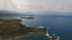Seascape with tropical island, beach, rocks and waves. Catanduanes, Philippines. The coast of the tropical island with the mountains and the rainforest on a stock video