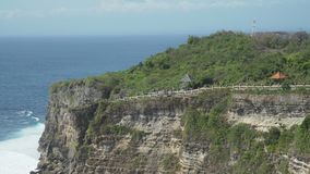 Pura Luhur Uluwatu, travelling from high cliff towards the sea. Coast at Uluwatu temple aerial view, Bali, Indonesia stock video