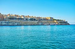 The fortified Valletta, Malta. The coast of Valletta with a view on its ramparts, stretching along the shore and medieval housing on hills` slopes, Malta Royalty Free Stock Photos