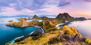 Coast view of Padar Island in a cloudy morning. With blue water surface and tourist boats, Komodo Island Komodo National Park, Labuan Bajo, Flores, Indonesia stock photos