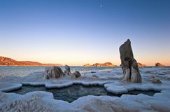 The coast of the winter cold sea at sunset. Royalty Free Stock Photography