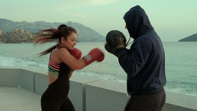 On the coast of woman in boxing gloves fulfills blows with coach.