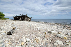 Coast with wooden shipwreck. Old wooden shipwreck at a stony coast Stock Photo