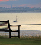 Coastal bench and yacht Stock Photography