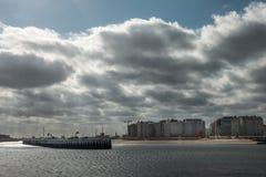 Coastal buildings along boardwalk in Oostende, Belgium. Oostende, Flanders, Belgium - September 18, 2018: Heavy cloudscape over wall of condominium buildings royalty free stock photo