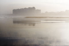 Coastal city reflected in the beach. Salinas, Asturias, north of Spain, between the fog and reflected in its beach in low tide Stock Photography