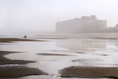 Coastal city reflected in the beach. Salinas, Asturias, north of Spain, between the fog and reflected in its beach in low tide. A small silhouette of a person Stock Image