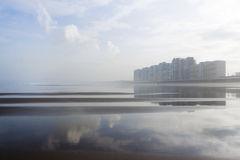 Coastal city reflected in the beach. Salinas, Asturias, north of Spain, between the fog and reflected in its beach in low tide Royalty Free Stock Photography
