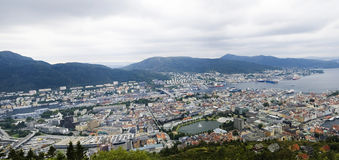 Coastal city or town. Panoramic view of coastal town or city and harbor with mountain range in background. Bergen, Norway Stock Image
