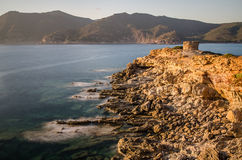 Coastal cliff with ruins of watch tower, Sardinia Stock Photography