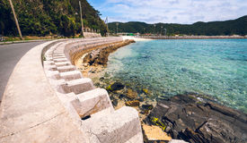 Coastal defence, Okinawa. Coastal defence on Zamami Island protecting the road from the sea with the port in the background Stock Photography