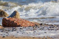 Coastal erosion. Destructive wave action. Focus on eroded concre. Coastal erosion. Destructive wave action. Focus on eroded partially uncovered concrete block Stock Image