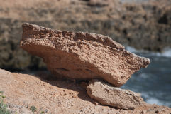 Coastal erosion - fallen chunk of red rock. Cabo Roig, Costa Blanca, Spain Stock Photo