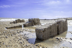 Coastal erosion revealing building foundations. Coastal erosion, These building foundations were uncovered by a tidal surge on the East coast of England in 2013 stock image