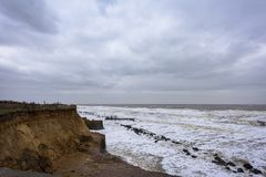 Coastal erosion taking place during a winter storm. UK, HAPPISBURGH - 18 MAR 2018: Coastal erosion taking place during a winter storm. Many homes have recently Royalty Free Stock Image