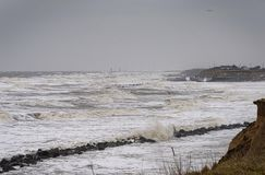 Coastal erosion taking place during a winter storm. UK, HAPPISBURGH - 18 MAR 2018: Coastal erosion taking place during a winter storm. Many homes have recently Royalty Free Stock Photography