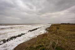Coastal erosion taking place during a winter storm. UK, HAPPISBURGH - 18 MAR 2018: Coastal erosion taking place during a winter storm. Many homes have recently Royalty Free Stock Photo