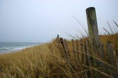 Coastal fence between sand dunes a beach Royalty Free Stock Image