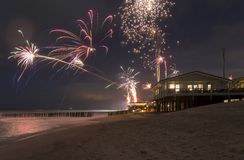 Coastal fireworks scenery. Coastal scenery at night including some fireworks at the beach near Domburg in Zeeland royalty free stock image
