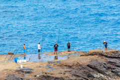 Coastal Fishing. Line of fishermen seeking a big catch on the rugged East Coast of Oahu, Hawaii Royalty Free Stock Photography