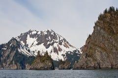 Coastal fjord Seward, Alaska. Rocky cliffs and snow covered mountains on a coastal fjord near Seward, Alaska Stock Image