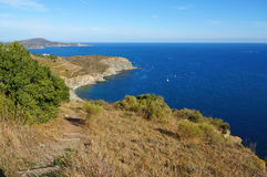 Coastal footpath to the Mediterranean sea. Coastal footpath leading to secluded cove on the rocky coast of the Mediterranean sea, Roussillon, Pyrenees Orientales Royalty Free Stock Photos