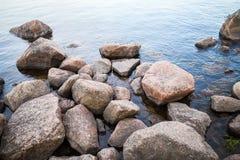 Coastal granite stones lay in still lake Stock Image
