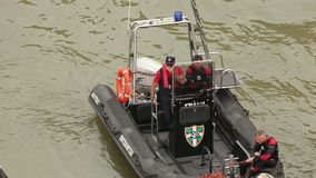 Coastal guards on duty in patrol boat, securing public safety on water and shore. Stock footage stock video