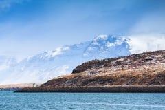 Coastal Icelandic landscape with coastal mountains. Coastal Icelandic landscape with snowy mountains under blue cloudy sky. Reykjavik area, Iceland Royalty Free Stock Photo