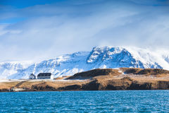 Coastal Icelandic landscape with snowy mountains. And small living house under dramatic blue sky. Reykjavik area, Iceland Stock Image