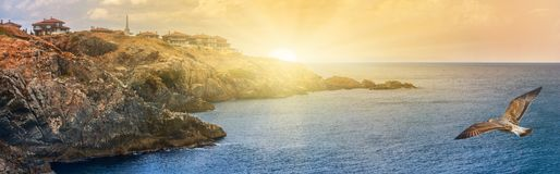 Coastal landscape banner, panorama - the rocky seashore with seagulls and the village of Sozopolis. Near city of Sozopol in Bulgaria royalty free stock images