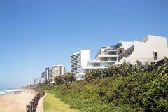 Coastal Landscape Beach and Sea at Umhlanga South Africa. Coastal landscape of green dune vegetation beach and sea against commercial and residential buildings Royalty Free Stock Image