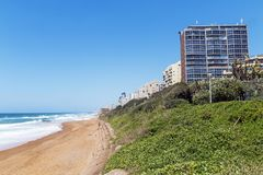 Coastal Landscape Beach and Sea at Umhlanga South Africa. Coastal landscape of green dune vegetation beach and sea against commercial and residential buildings Stock Image
