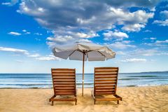 Coastal landscape - Beach umbrellas and loungers on the sandy seashore. The Kavatsi bay near city of Sozopol in Bulgaria stock image