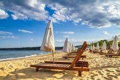 Coastal landscape - Beach umbrellas and loungers on the sandy seashore. The Kavatsi bay near city of Sozopol in Bulgaria royalty free stock photography