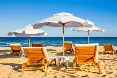 Coastal landscape - Beach umbrellas and loungers on the sandy seashore. The Kavatsi bay near city of Sozopol in Bulgaria royalty free stock photos