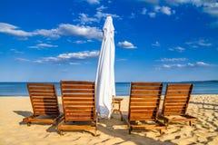 Coastal landscape - Beach umbrellas and loungers on the sandy seashore. The Kavatsi bay near city of Sozopol in Bulgaria royalty free stock image