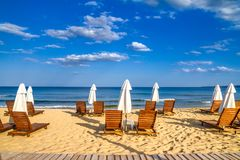 Coastal landscape - Beach umbrellas and loungers on the sandy seashore. The Kavatsi bay near city of Sozopol in Bulgaria royalty free stock images
