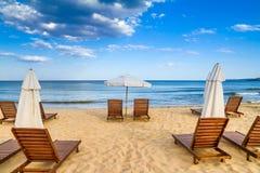 Coastal landscape - Beach umbrellas and loungers on the sandy seashore. The Kavatsi bay near city of Sozopol in Bulgaria stock photography