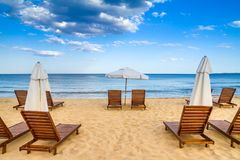 Coastal landscape - Beach umbrellas and loungers on the sandy seashore. The Kavatsi bay near city of Sozopol in Bulgaria Stock Images