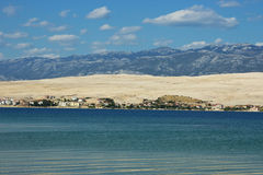 Coastal Landscape with Blue Mountains and Small Village. With White Clouds Above Stock Photo