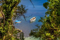 Coastal landscape - the boats in bay with view through trees Stock Photo
